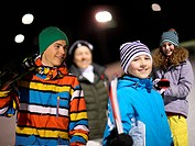 Boys and girls on ski slope at night
