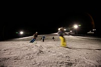 Girls and boys skiing at night, blurred motion