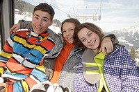 Girls and teenage boy traveling in cable car on ski slope