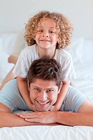 Smiling father and child lying on bed