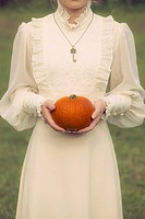 a woman in a victorian dress is holding a pumpkin