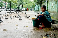 Women selling corn to feed pigeons at downtown Yangon