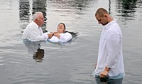 Pastor plunges young woman into the water during baptism, Pennsylvania, USA