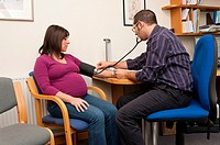 GP Doctor checking pregnant woman blood pressure