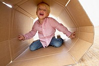 Four year old boy playing in a cardboard box