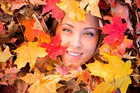 Blonde haired woman outdoors in leaf pile