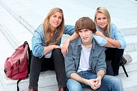 Three teenage friends sat on steps