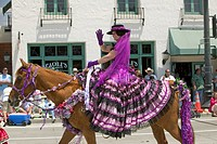 Woman with purple Spanish dress riding horse during opening day parade down State Street, Santa Barbara, CA, Old Spanish Days Fiesta, August 3_7, 2005
