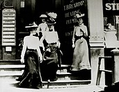 Group of Fashionable Women in Hats and Long Skirts Leaving Building, Circa 1900