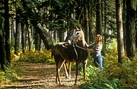 Woman with horse by the reins on trail in Autumn