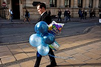 A man walking with some balloons in Cheltenham