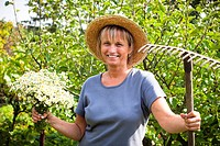 Portrait of happy mature woman holding flowers and rake in the garden