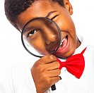 Close up of clever scientist school boy with magnifying glass, isolated on white background
