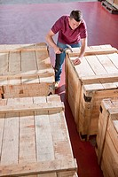 Worker hammering lid on crate in warehouse