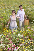 Smiling couple with picnic basket in sunny meadow with wildflowers