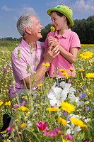 Smiling grandfather and granddaughter among wildflowers in sunny meadow