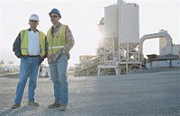Two men standing near industrial plant