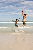 Father and Son on the beach, jumping.
