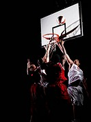 Basketball players reaching for the ball