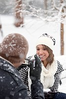 man taking woman´s photo in snowy park