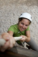 Young woman climbing up a rope
