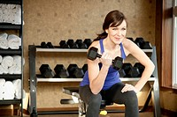A fit, healthy woman weight lifting in a gym.