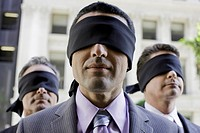 Three blindfolded businessmen