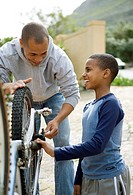 Father and son mending bike outdoors