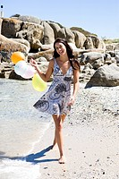 Girl walking on beach holding balloons