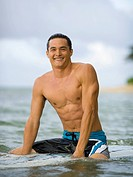 WR0858680 Portrait of a young man sitting on a surfboard