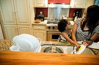 Young girl helps Mom clean dishes