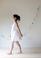 Girl walking in front of paper decoration