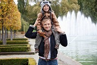 Portrait of father carrying son on his shoulders at park