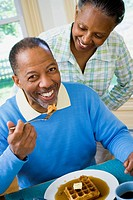 Close_up of a senior man having breakfast with a senior woman behind him