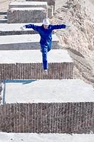 worker jumping between blocks of marble