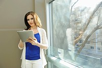 Young businesswoman using a tablet in the hallway of an office building, edmonton, alberta, canada