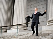 Low angle view of a male lawyer laughing and walking down the steps of a courthouse