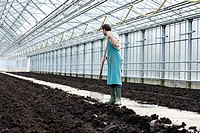 Germany, Bavaria, Munich, Mature man digging soil with garden fork in greenhouse