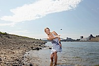 Germany, Cologne, Young woman skipping stones in river (thumbnail)