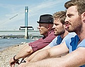 Germany, Cologne, Young men sitting on riverbank