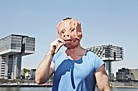 Germany, Cologne, Young man with pig mask eating sausage
