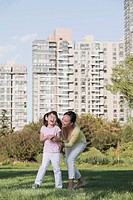 Chinese mother and daughter playing in park