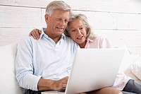 Spain, Senior couple checking emails on laptop, smiling