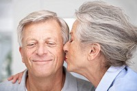 Spain, Senior woman kissing to man, close up