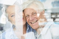 Spain, Senior couple behind window, smiling