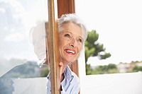 Spain, Senior woman looking through window, smiling