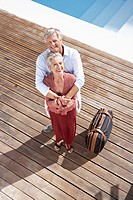Spain, Senior couple standing with suitcase at swimming pool, smiling, portrait