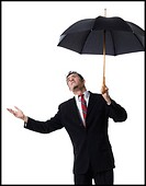 Businessman holding an umbrella and looking up