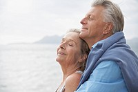 Spain, Senior couple on beach at Atlantic, smiling