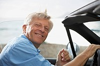 Spain, Senior man in convertible car, smiling, portrait